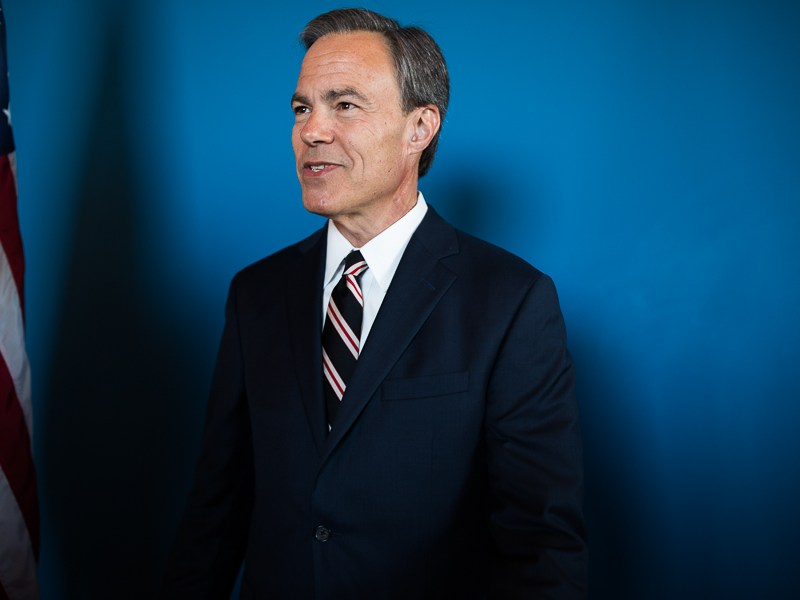 Texas House Speaker Joe Straus waits for his next photo opportunity as he stands next to an American flag. Photo by Scott Ball.