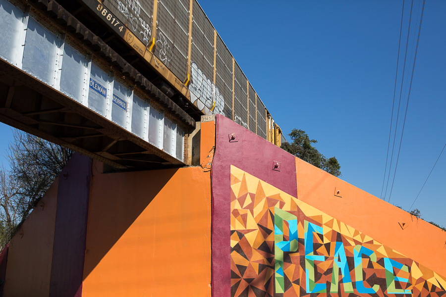 A train passes over the Coleman Underpass bridge where the mural is located. Photo by Scott Ball.