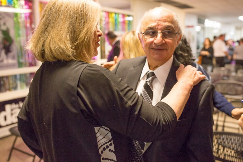 Harvey Najim hugs an attendant following the press conference. Photo by Scott Ball.