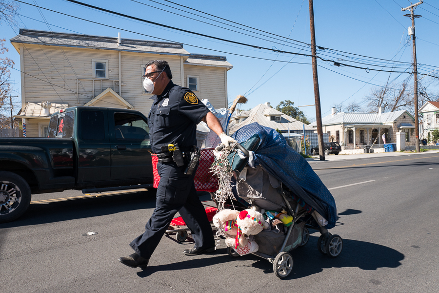 SAPD Officer Gomez walks a grocery cart and stroller filled with various items to large dump trucks. Photo by Scott Ball.