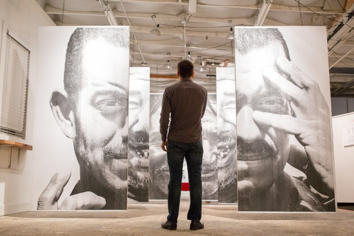 A guest looks through the panels of canvassed photographs by artist Daniela Riojas. Photo by Scott Ball.