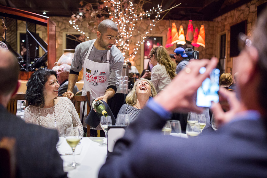 San Antonio Spurs Point Guard Tony Parker serves wine to Judy Perry as she laughs during a photo opportunity from across the table. Photo by Scott Ball.