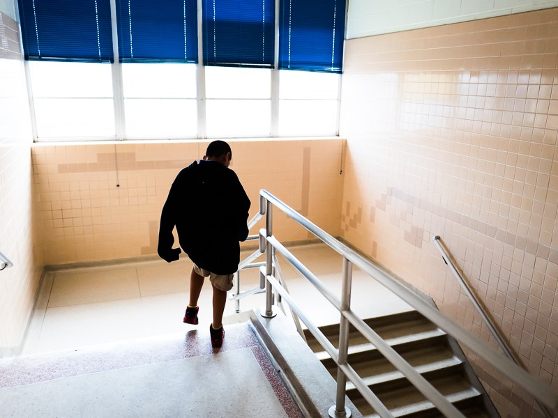 A student walks down the stairs at Stewart Elementary School. Photo by Scott Ball.