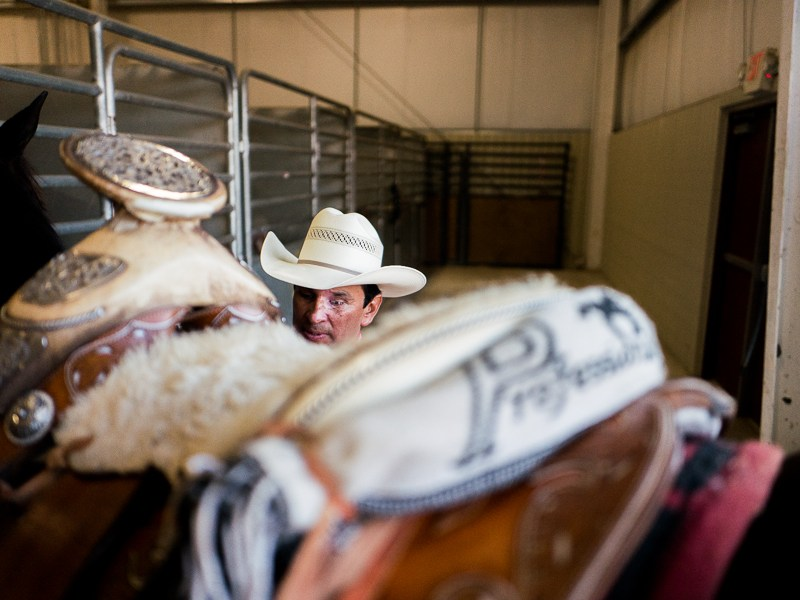 Tomás Garcilazo prepares a saddle on one of his horses. Photo by Scott Ball.