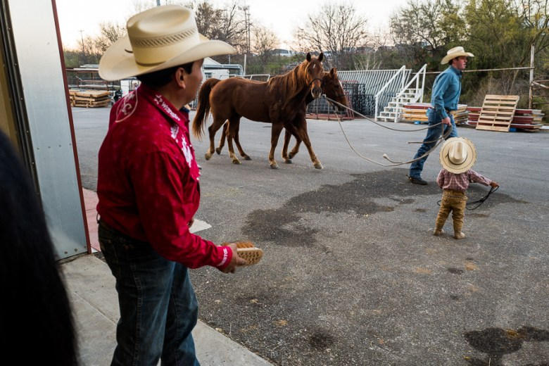 Tomás Garcilazo pauses from brushing his horses hair as his son Louis, 17 months, swings his rope as a rodeo contestant walks by with two horses. Photo by Scott Ball.