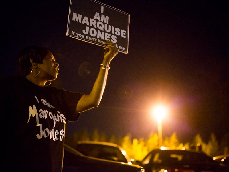 """Protestor Ivory Rice holds up a sign that reads """"I Am Marquise Jones"""". Photo by Scott Ball."""