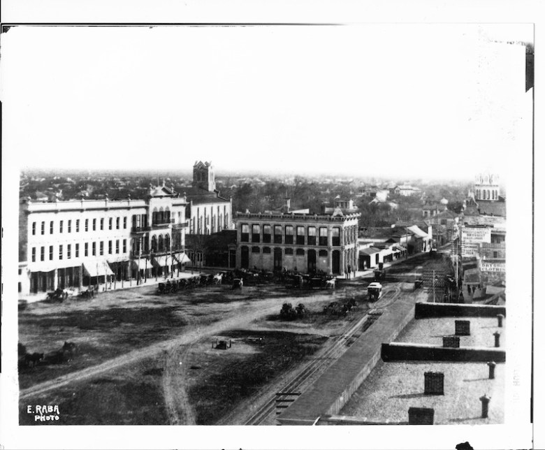 This photo, taken looking south, shows an unpaved Alamo Plaza, c. 1882-1886. (Left to right) The three-story Menger Hotel; St. Joseph's Catholic Church, with its steeple still under construction; the Gallagher Building (center) and the Dullnig Building, distinguished by its dome (upper right). A streetcar travels north up the plaza. Photo courtesy of the San Antonio Conservation Society Foundation