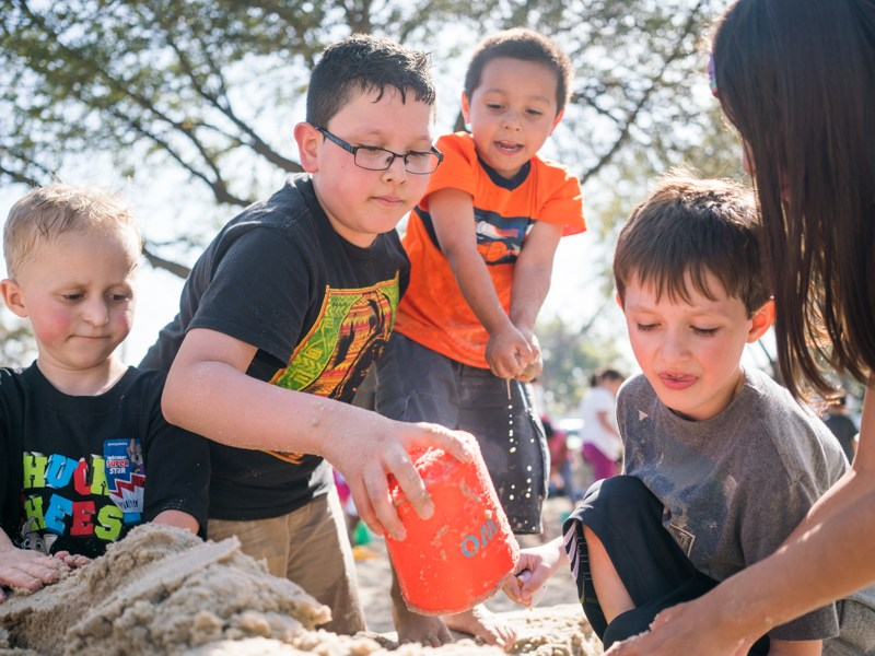 Damian and Henry work with friends to build a dam and sand castle. Photo by Kathryn Boyd-Batstone