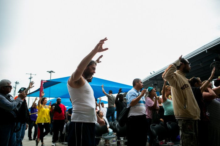 Have For Hope residents raise their hands up to God in prayer. Photo by Kathryn Boyd-Batstone