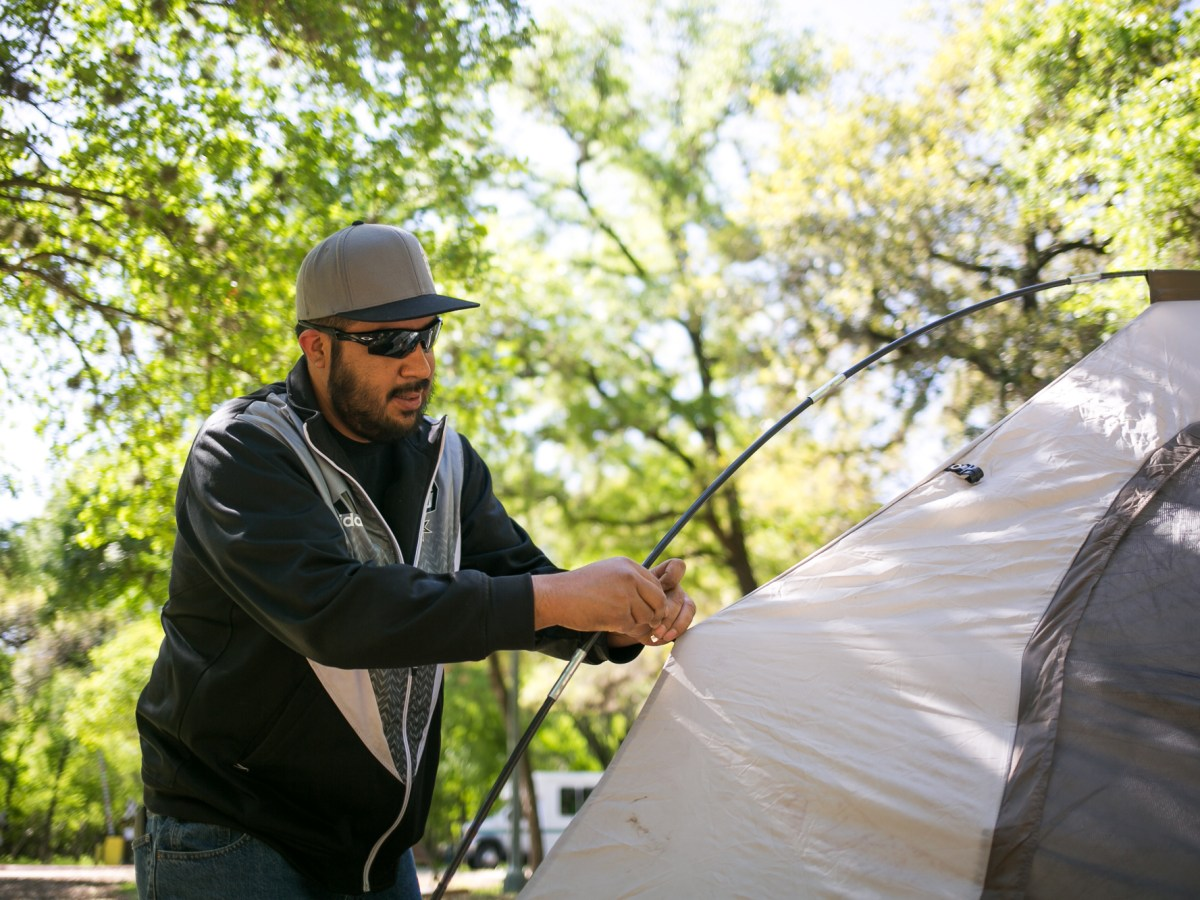 Justin Lopez works on setting up a tent for his family. Photo by Kathryn Boyd-Batstone