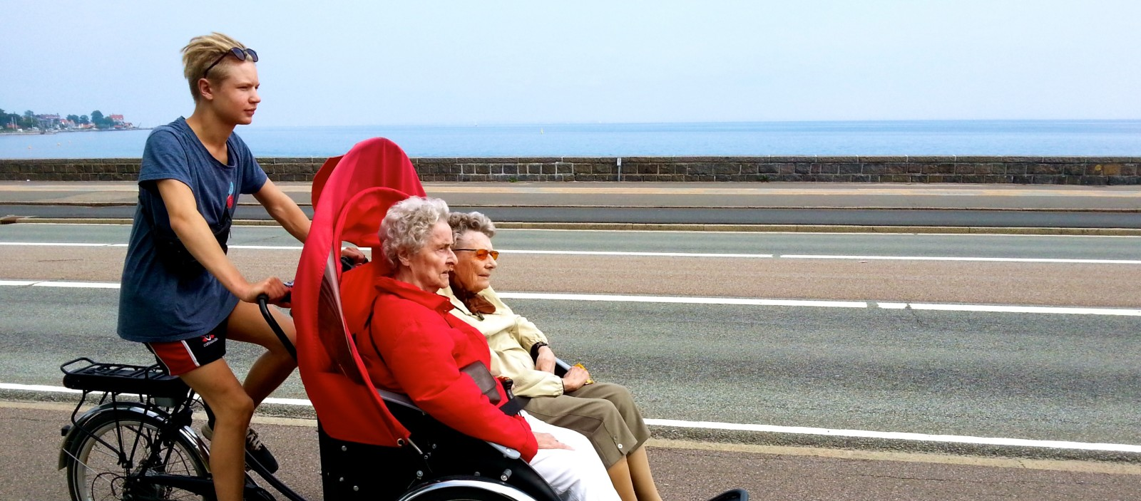 A young man uses a trishaw to show two women around town. Photo by Ole Kassow, courtesy of Cycling Without Age.