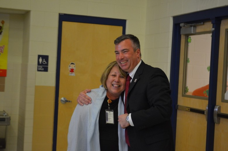Driggers Elementary Principal Mary Helen Cover hugs her husband, Terry, after being surprised by a school-wide assembly in her honor. Photo by Camille Garcia.