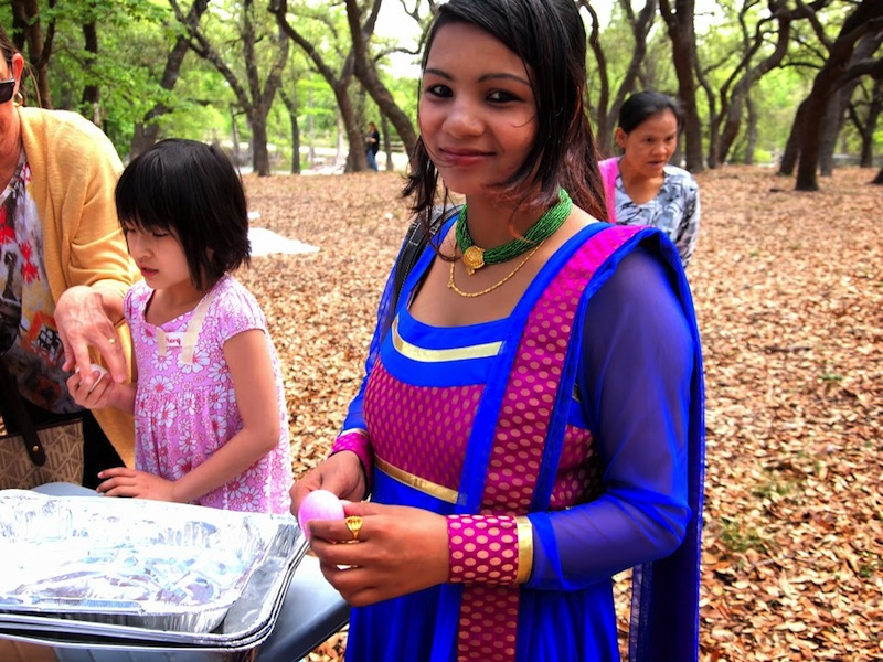A young Hindi woman holds an easter egg. Photo by Sheena Maria Connell.