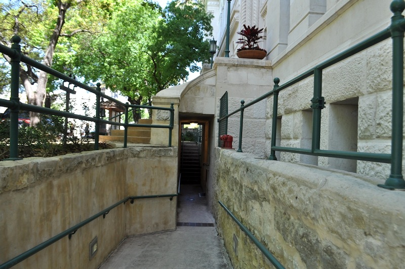 The ADA ramp narrows and it descends to the back, basement entrance of City Hall. Photo by Iris Dimmick.