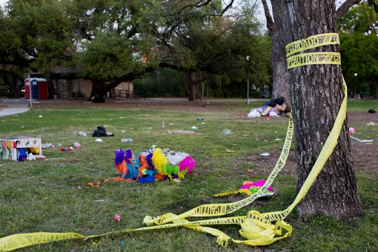 Caution tape, a piñata, and litter is strewn across grass at Brackenridge Park. Photo by Scott Ball.