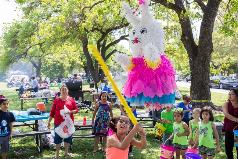 Children of the Fernandez family wait patiently as a child pummels an Easter bunny themed piñata. Photo by Scott Ball.
