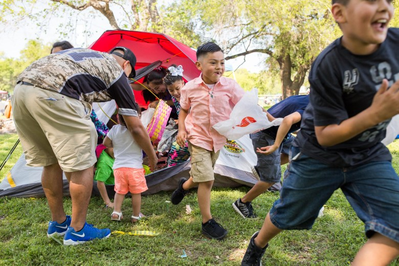 Children from the Fernandez family storm out of a tent where they were kept while parents hid easter eggs. Photo by Scott Ball.