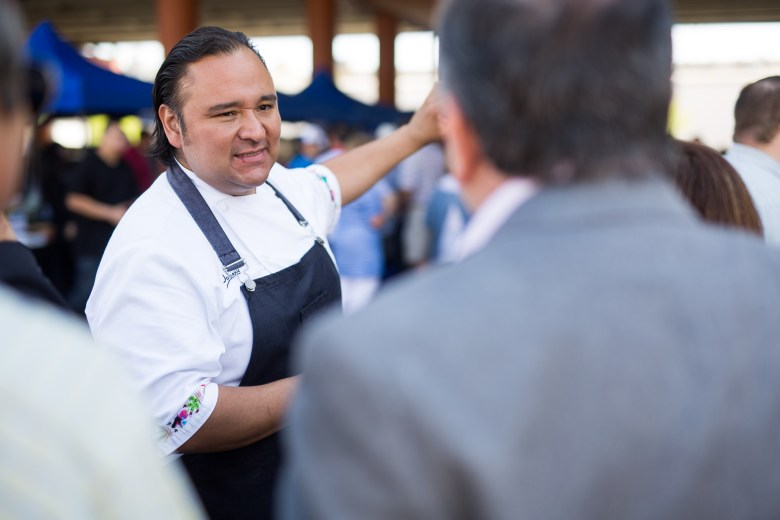Chef Johnny Hernandez points friends in the direction of paella tents. Photo by Scott Ball.