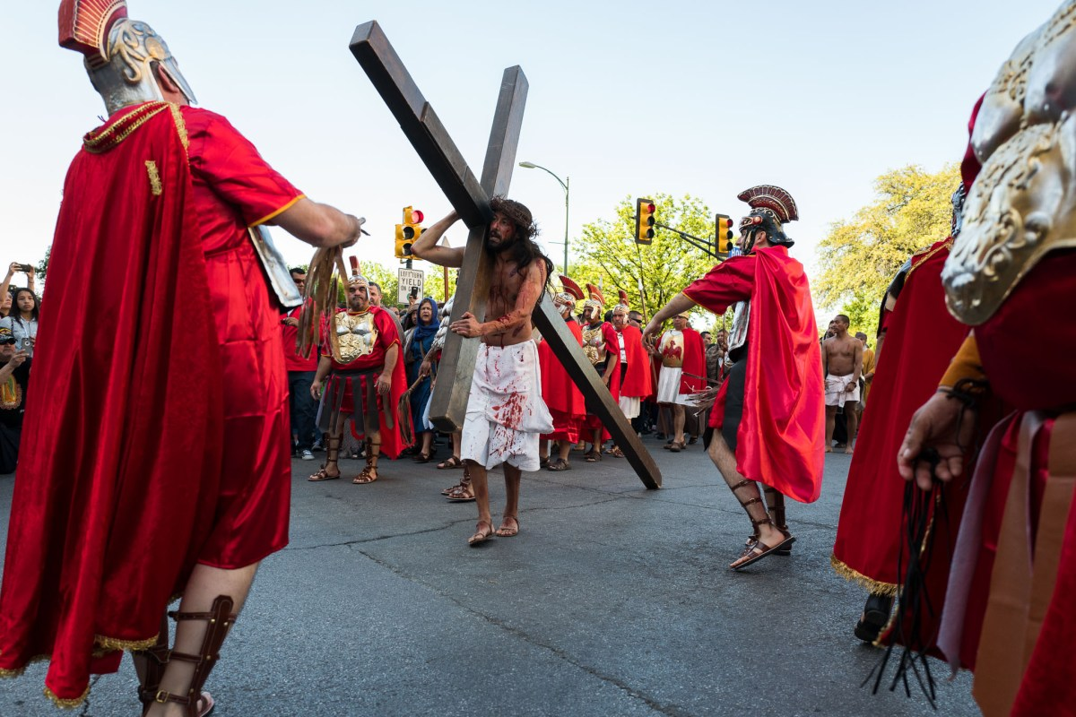 The cross is carried down Houston Street as Roman soldiers whip and batter Jesus. Photo by Scott Ball.