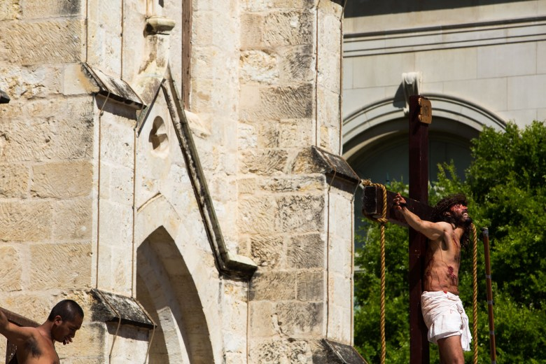 An actor hangs from a cross during a reenactment of the crucifixion of Jesus Christ.
