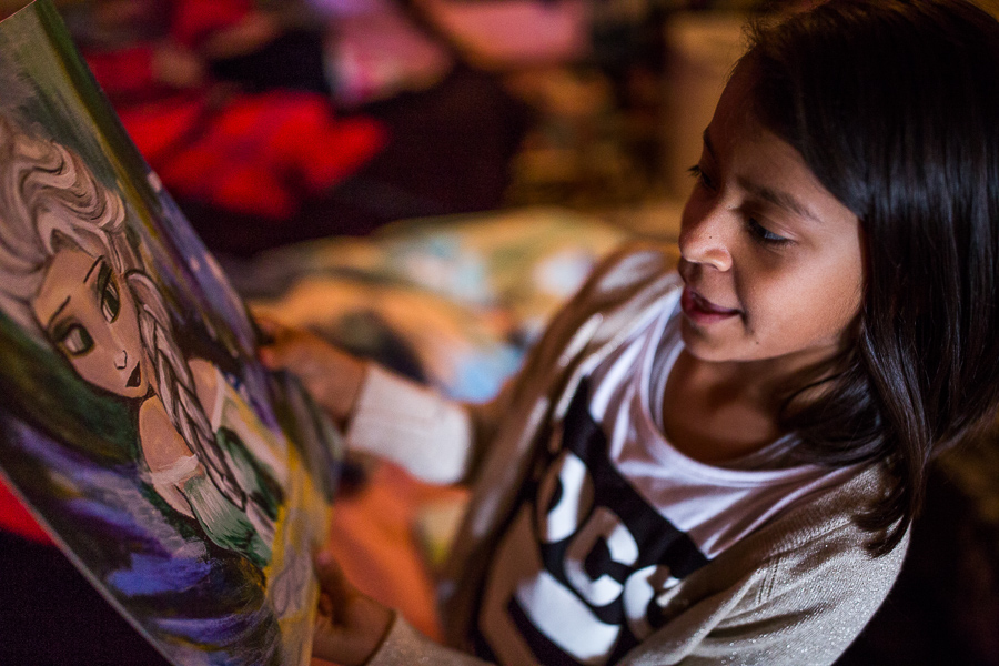 Angelica spends time examining the painting her mother made her of the popular Disney character Elsa from the film Frozen. Photo by Scott Ball.