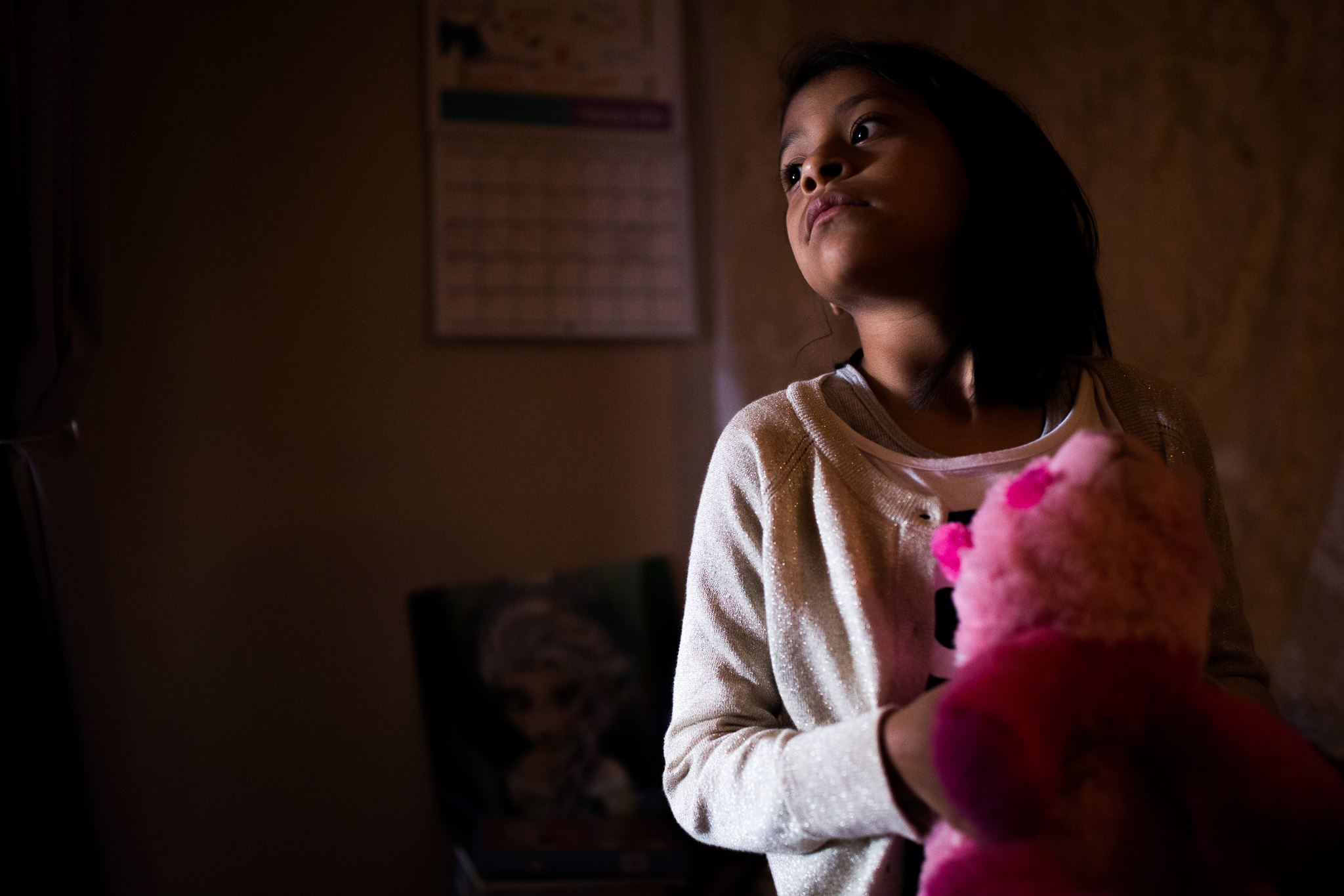 Angelica peers outside of her shared room door to the living room where her cousin calls her name. Photo by Scott Ball.