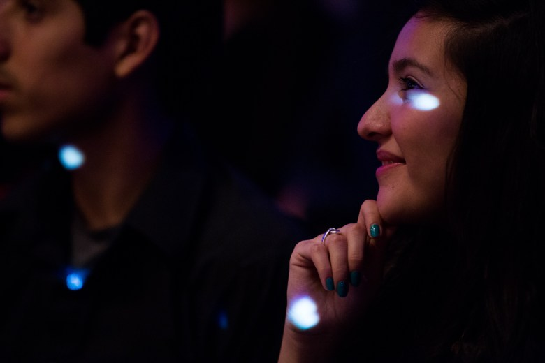 An audience member smiles during a performance as light passes over her face. Photo by Scott Ball.