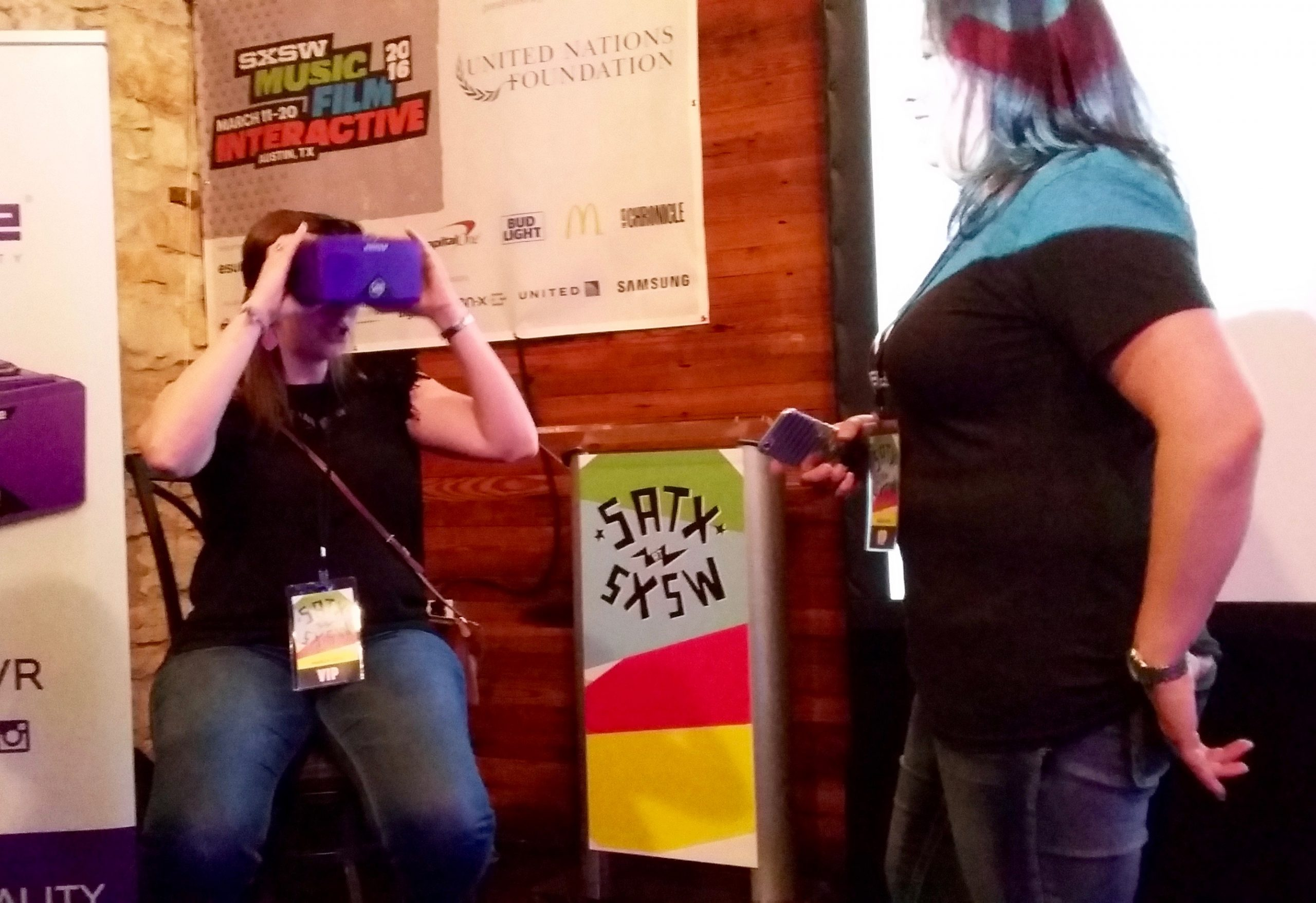 Crystal Stein of Austin (left) visits Merge VR's booth, as Choose San Antonio volunteer Jennifer Alaniz looks on, at a startup community party at Austin's Old School Bar and Grill on Friday, March 11, 2016. Photo by Edmond Ortiz