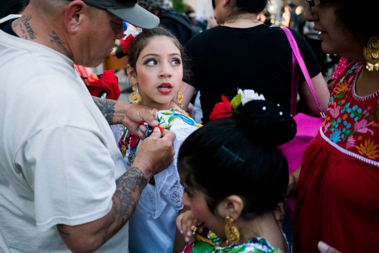 A young folklórico dancer gets a Fiesta medal pinned to her costume.
