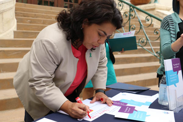 """Councilwoman Rebecca Viagran (D-3) signs the pledge at the Rape Crisis Center """"Start By Believing"""" Campaign launch on the steps of City Hall. Photo by Bria Woods."""