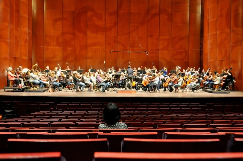 Associate Conductor Akiko Fujimoto listens to the San Antonio Symphony rehearse for their weekend concert. Photo by Iris Dimmick.