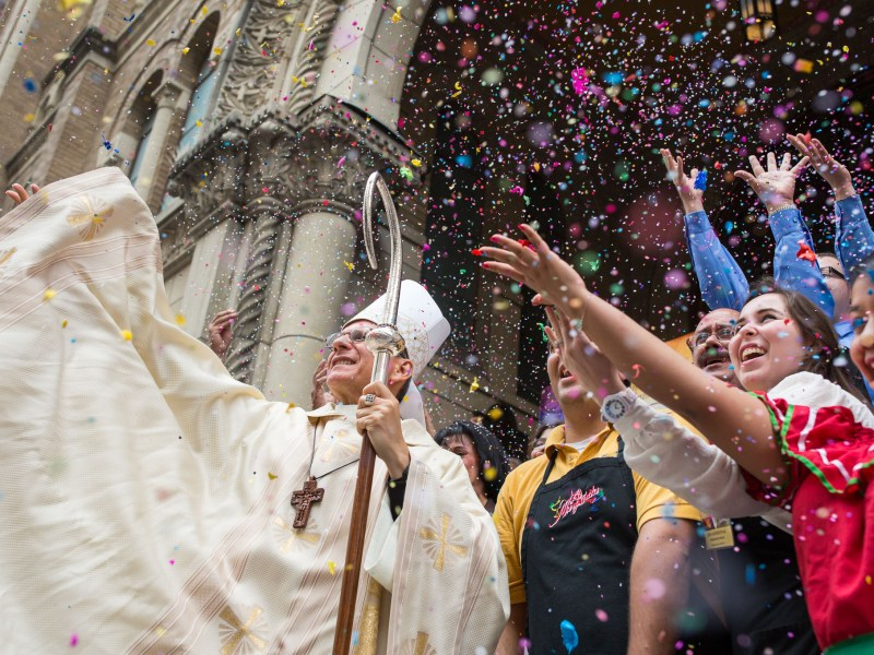 Archbishop Gustavo García-Sille along with members of the hospitality community throw confetti into the air after crushing cascarones. Photo by Scott Ball.