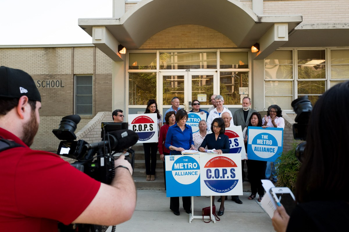 Members of C.O.P.S and Metro Alliance along with at least one SAISD employee stand on the steps before a SAISD board meeting asking for higher wages for it's lowest income employees. Photo by Scott Ball.