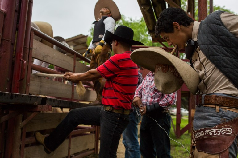 Charros stand around and prepare for their moment as Daniel Arguelles looks up to the sky as rain falls. Photo by Scott Ball.