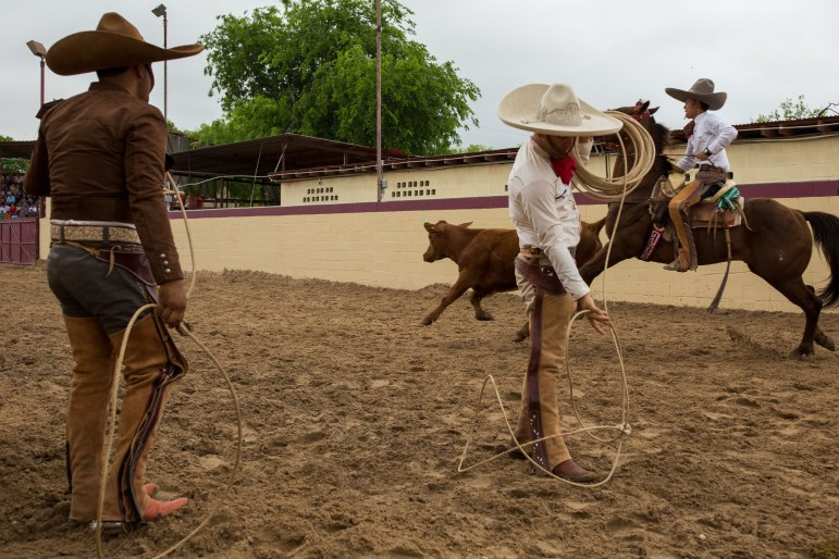 Charros practice their roping skills as Edmundo Rios attempts to grapple a calf's tail. Photo by Scott Ball.
