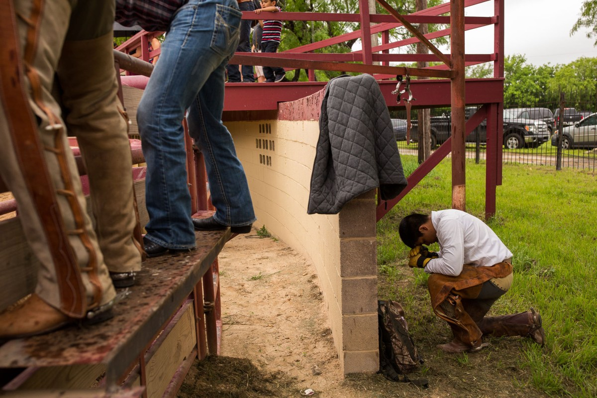 Daniel Arguelles prays moments before it is his turn to ride a bull. Photo by Scott Ball.