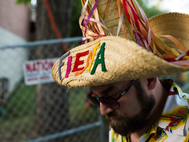 An attendee sifts through a crowd while wearing a Fiesta branded sombrero. Photo by Scott Ball.