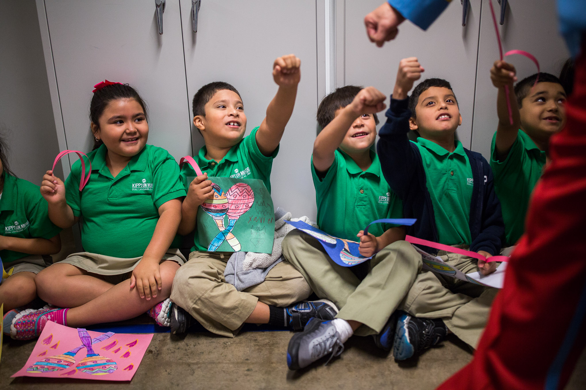 KIPP San Antonio students reach high to bump fists with a member of the Texas Cavaliers. Photo by Scott Ball.