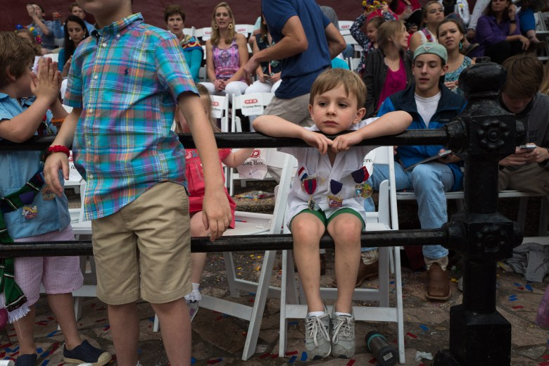 Luke, 5, dangles from a railing while watching the parade. Photo by Scott Ball.