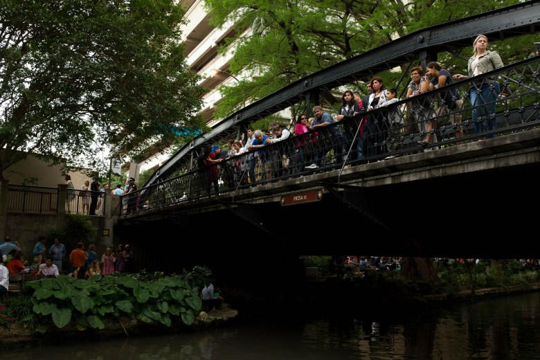 Guests line the Presa Street bridge in anticipation of decorated river barges. Photo by Scott Ball.