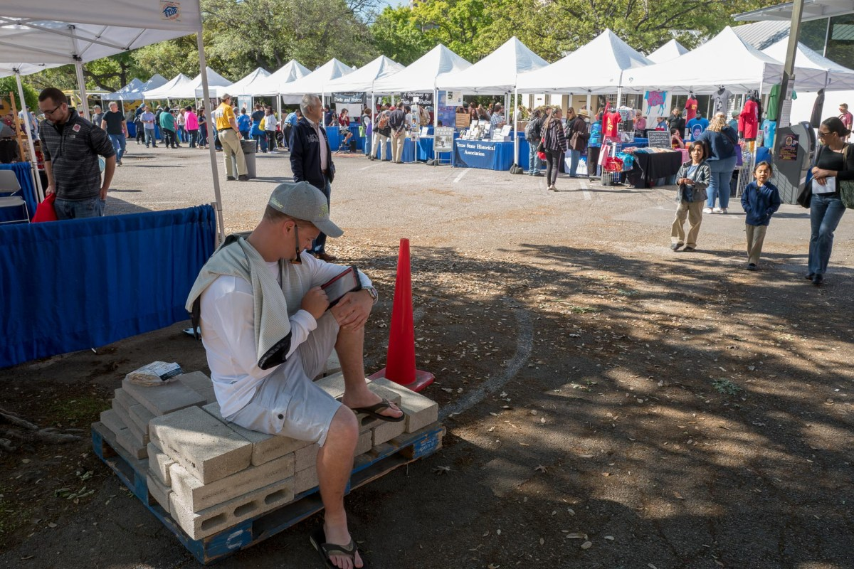 A festival attendee gets an early morning read in before the large crowd arrives. Photo by Scott Ball.