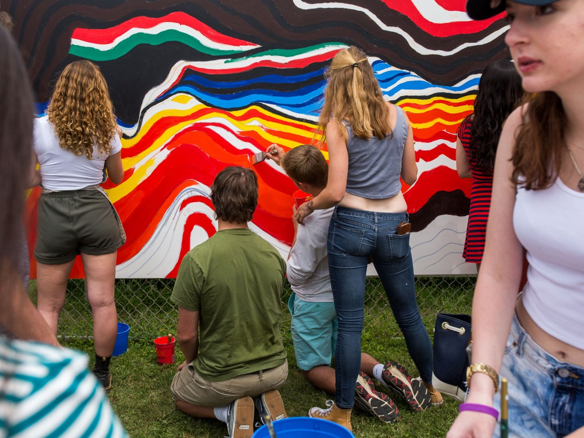 Students at Saint Mary's Hall gather around a group mural created and designed by local artist Alex Rubio during the ISAS Art Festival.