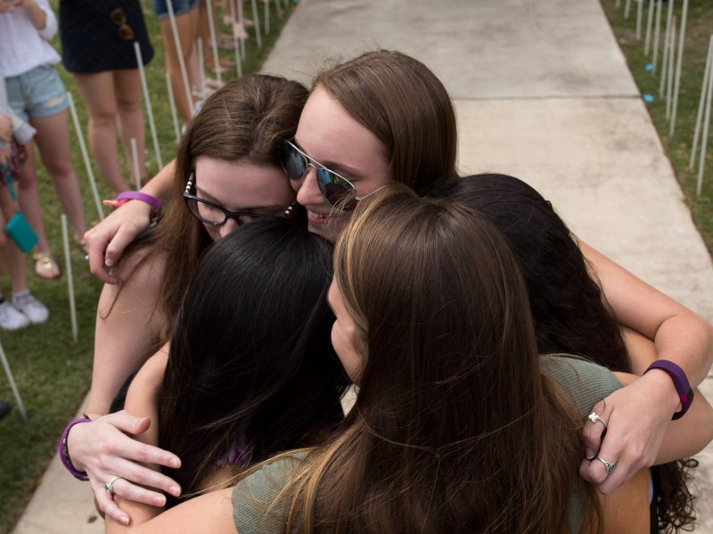 Nikke Kimichik, Daryl Lewis, McKenna Richards, Nicole Free, and Jaya Gupta join in a group hug after attending a student made mock marriage ceremony. Photo by Scott Ball.