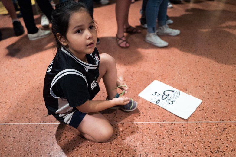 Arianna, 8, ties her shoe while watching a dance performance by Team Energy. Photo by Scott Ball.