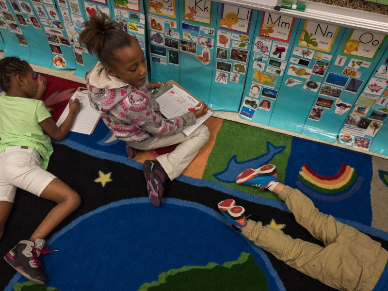 Kindergarten students Mariah and Adele work on a classroom station based reading exercise. Photo by Scott Ball.