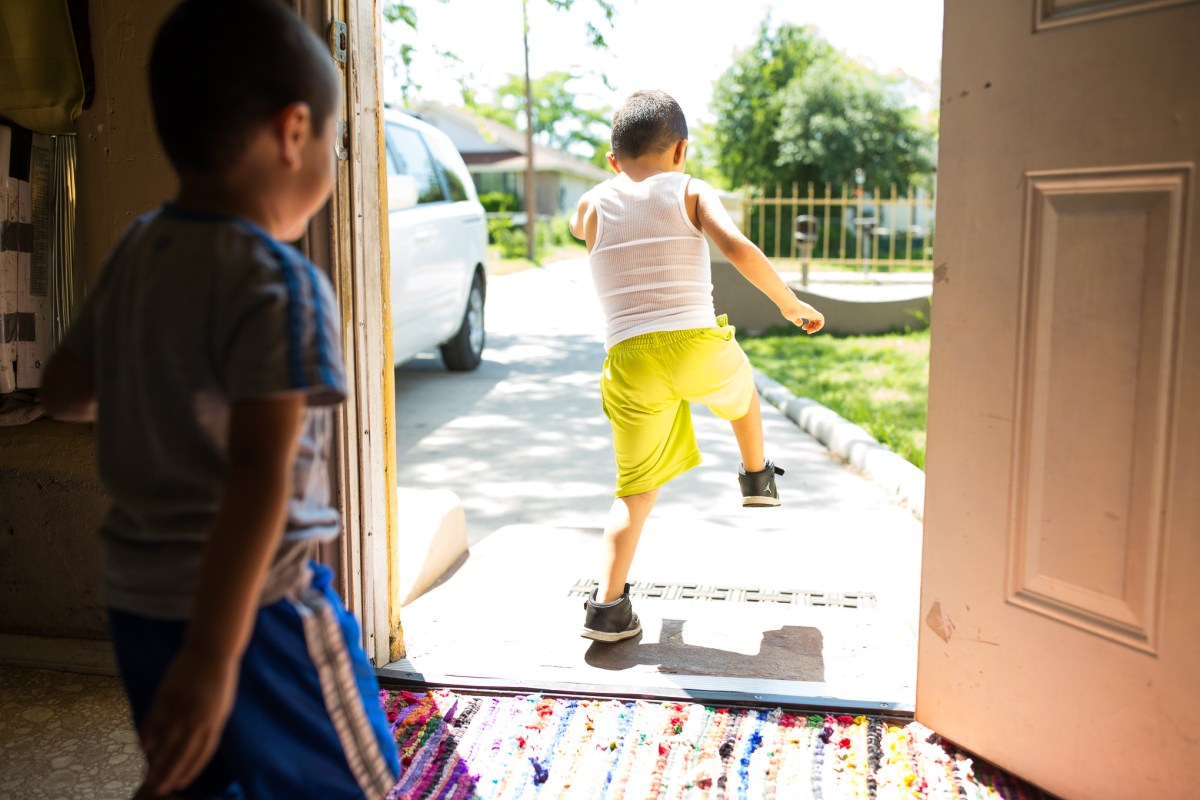 Brothers Isaiah, 4 and Adam, 5 run through the front door of their house for much needed play time. Photo by Scott Ball.