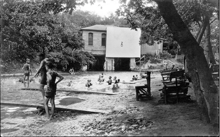 A historic photo of Lambert Beach with a screen possibly for projecting film covering the pump house. Photo courtesy of the Brackenridge Park Conservancy.