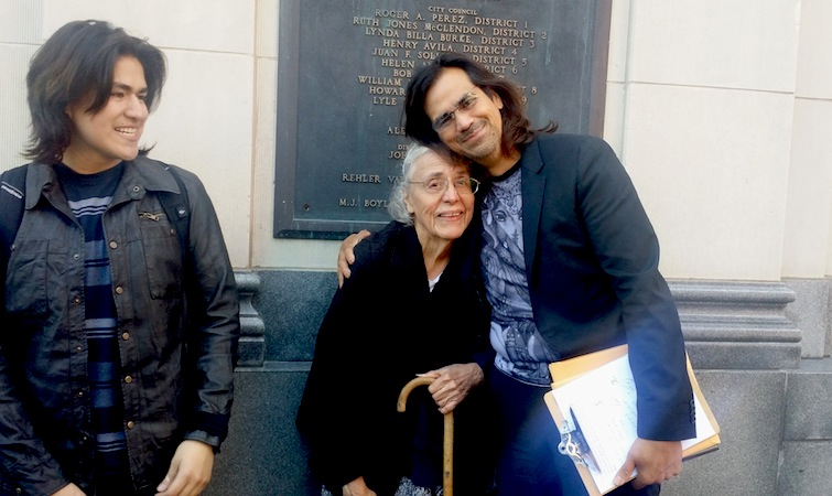 Andrew Guerra hugs his neighbor and customer, Nora, outside the Municipal Plaza Building. Photo by Iris Dimmick.