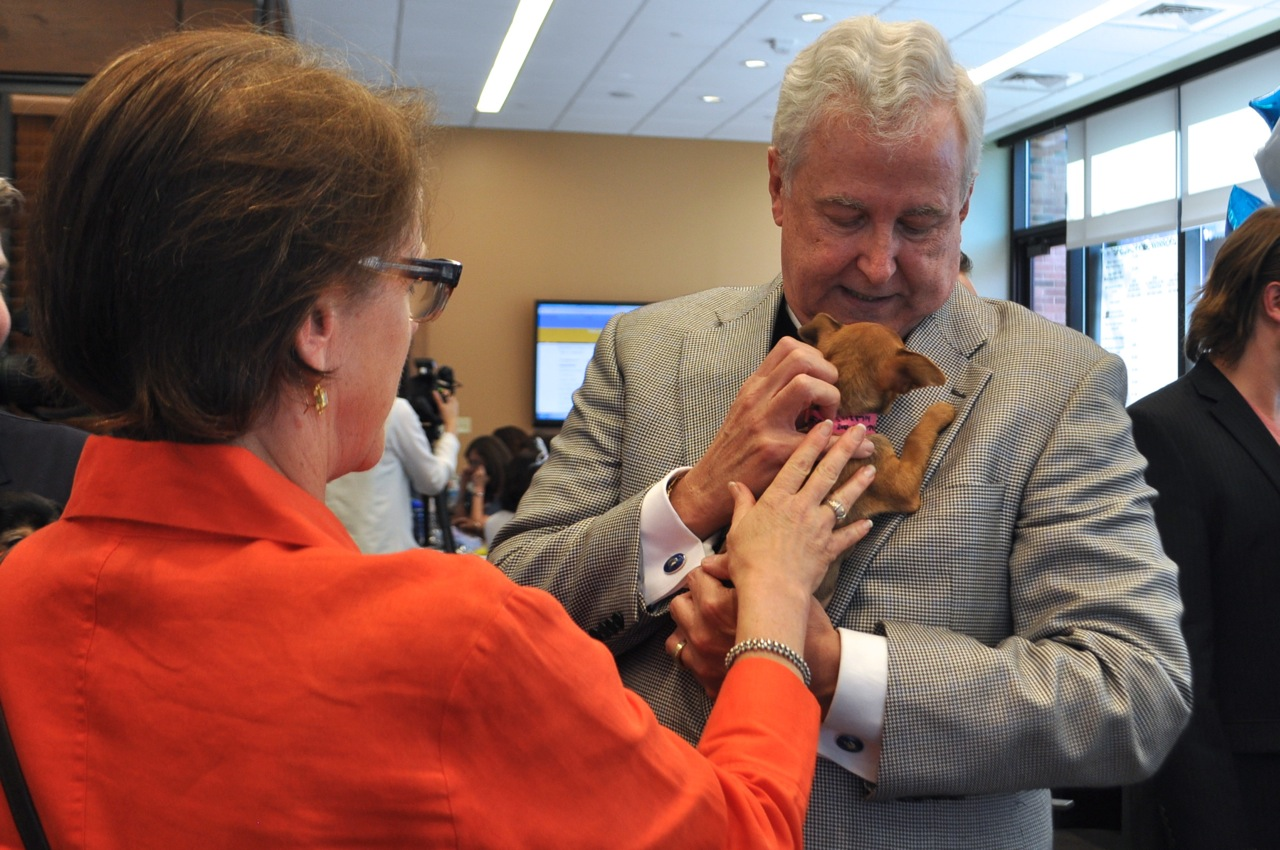 """San Antonio Area Foundation President and CEO Dennis Noll comforts Dottie, a puppy from the San Antonio Humane Society, after the announcement. """"You're sad about the website, too?"""" Noll said. Photo by Iris Dimmick."""