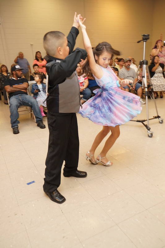 A dance couple executes a merengue dance movement at the Edgewood ISD district-wide ballroom dancing competition. Photo courtesy of Nuvo Multimedia.